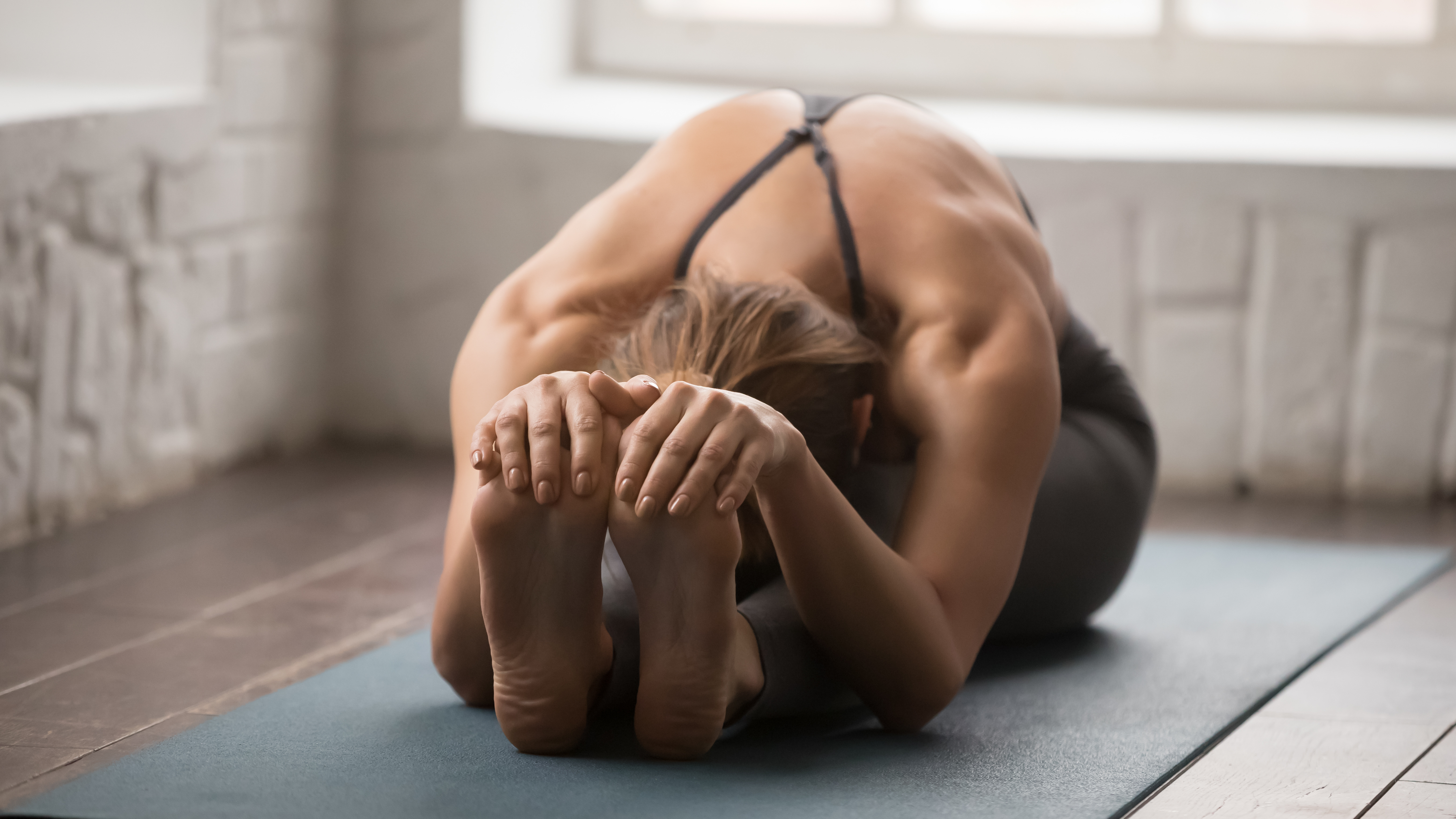 Beautiful woman practicing yoga, Seated forward bend pose, paschimottanasana